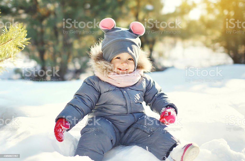 Happy smiling little child playing on snow in winter day stock photo
