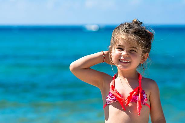 glücklich lächelnden kleinen mädchen im meer, blauer, meer im hintergrund - küstenfamilienzimmer stock-fotos und bilder