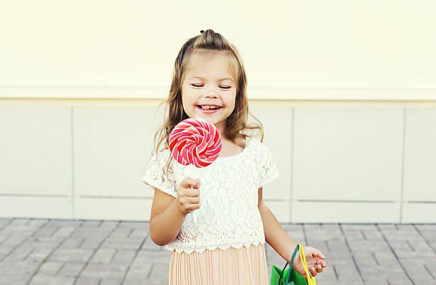 kind glücklich lächelnd mädchen mit süßen lutscher karamell - taschen von liebeskind stock-fotos und bilder