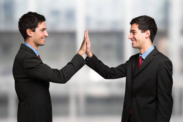 Happy smiling man high fiving to himself stock photo