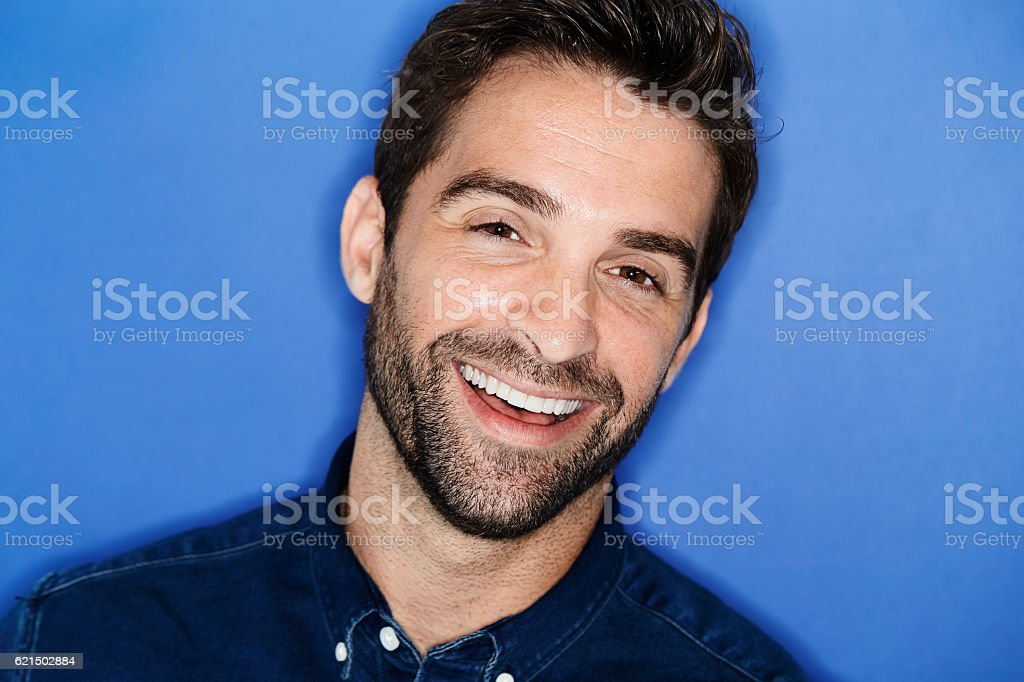Happy smiling man in blue studio, close up foto stock royalty-free
