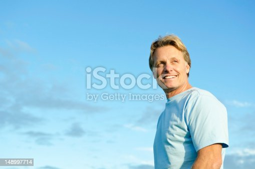 color portrait photo of a happy smiling blond haired man in his forties wearing a blue t'shirt against a blue sky backround.