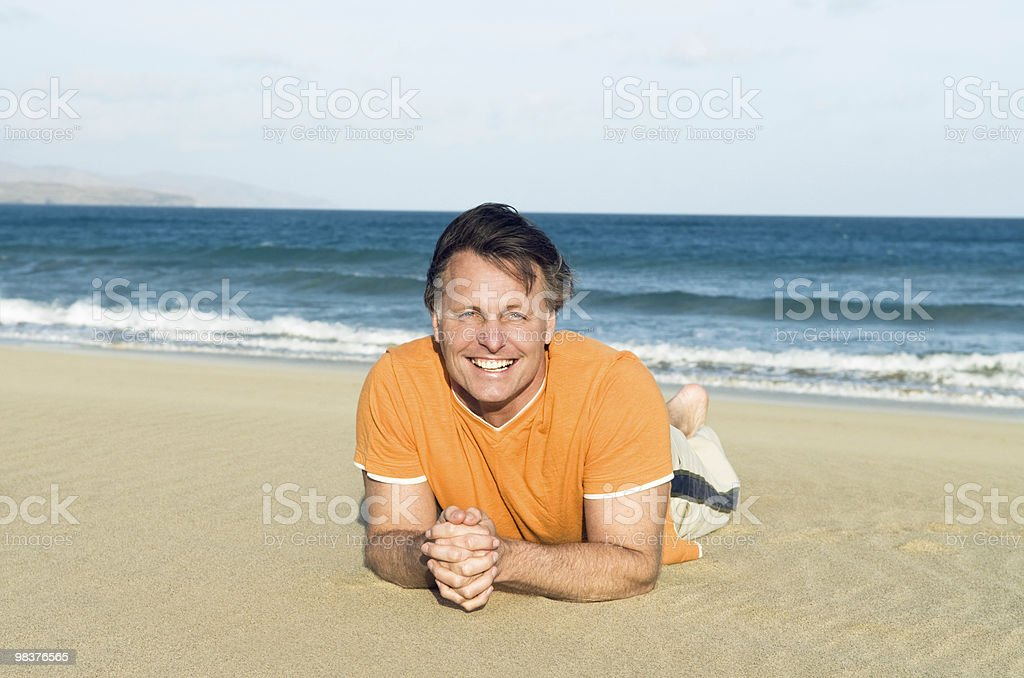happy smiling man laying on the beach. royalty-free stock photo