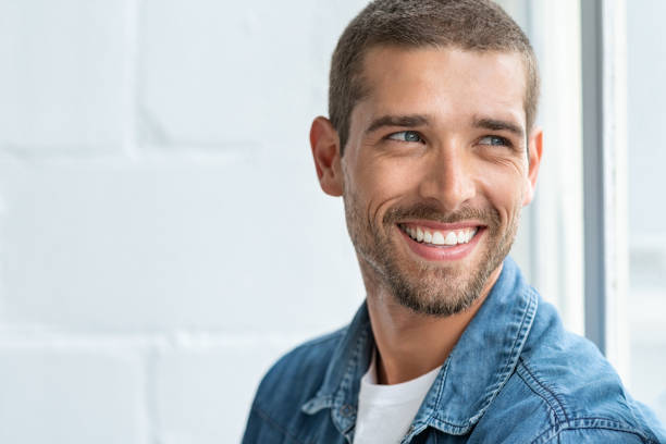 Happy smiling man looking away Confident young man looking away with big smile. Happy handsome guy looking through window thinking about the future. Closeup face of smiling casual man imagine with copy space. teeth stock pictures, royalty-free photos & images