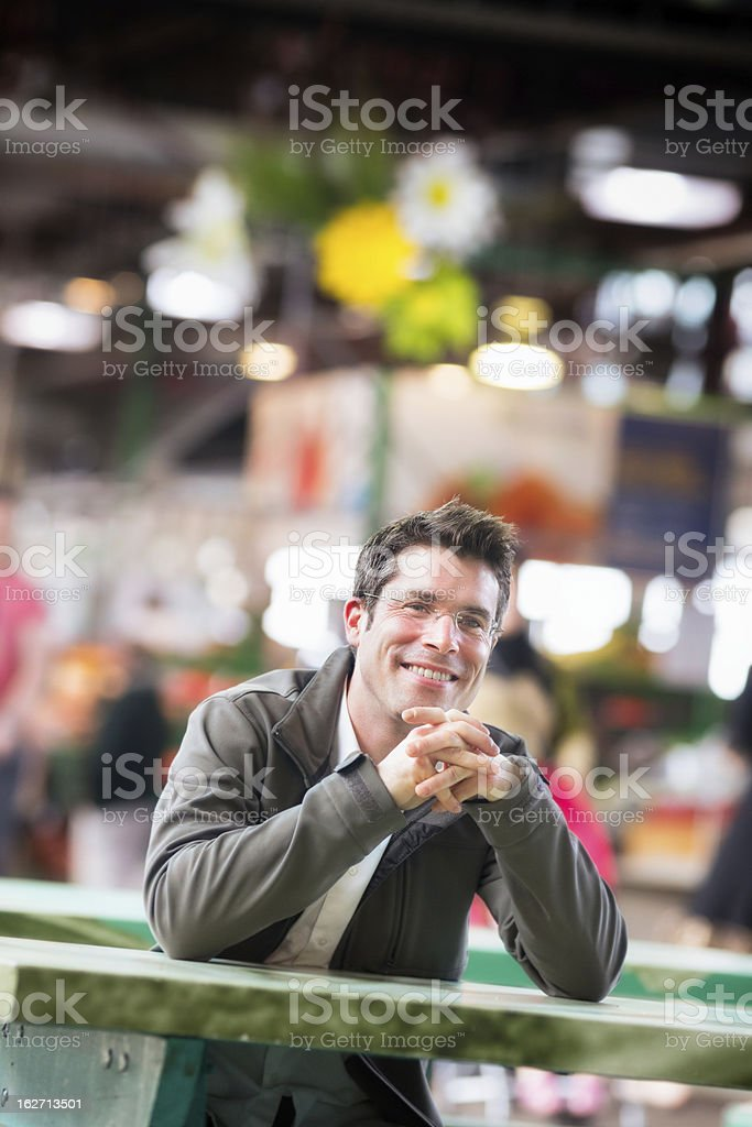 Happy smiling man sitting at farmer's market vertical royalty-free stock photo