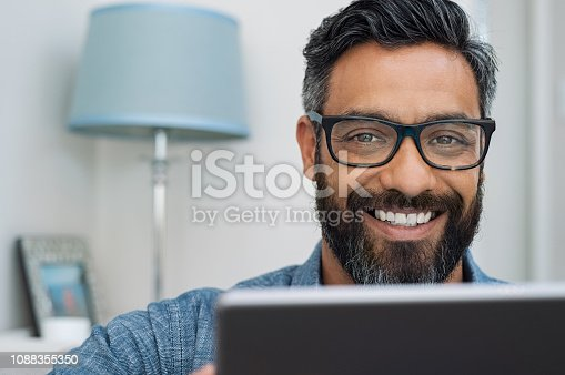 Closeup of businessman with beard wearing glasses and working on laptop while looking at camera. Mature mixed race man relaxing at home with computer. Handsome hispanic man working at home and using laptop.