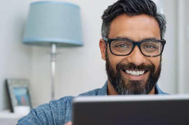 Happy smiling man working on laptop Closeup of businessman with beard wearing glasses and working on laptop while looking at camera. Mature mixed race man relaxing at home with computer. Handsome hispanic man working at home and using laptop. indian male stock pictures, royalty-free photos & images
