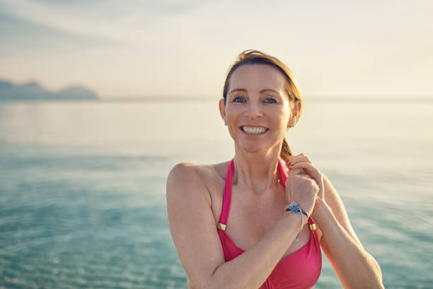 happy smiling middle-aged woman at the seaside - older women bikini stock pictures, royalty-free photos & images
