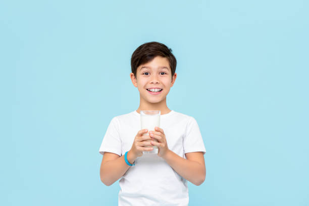 Happy smiling Mixed race boy drinking fresh milk isolated on light blue studio background stock photo