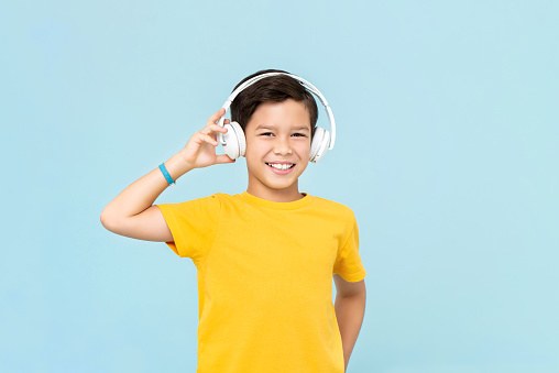 Happy smiling mixed-race boy wearing wireless headphones listening to music isolated on light blue background
