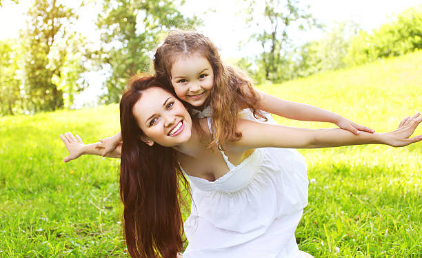 Happy smiling mother and daughter child having fun together outd Happy smiling mother and daughter child having fun together outdoors in sunny summer day mother and child stock pictures, royalty-free photos & images