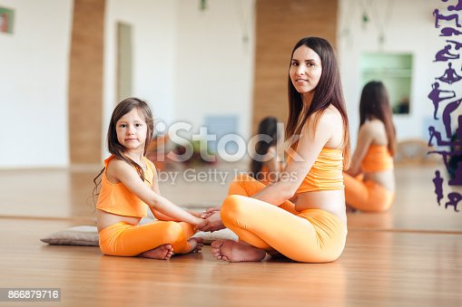 istock Happy smiling mother and daughter in bright orange sport suits sitting on the floor in the gym, hugging, looking at the camera, full-length, Hold hands 866879716