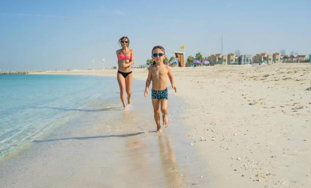 glücklich lächelnd, mutter und sohn spielen und laufen am strand. konzept der freundlichen familie - dubai urlaub stock-fotos und bilder