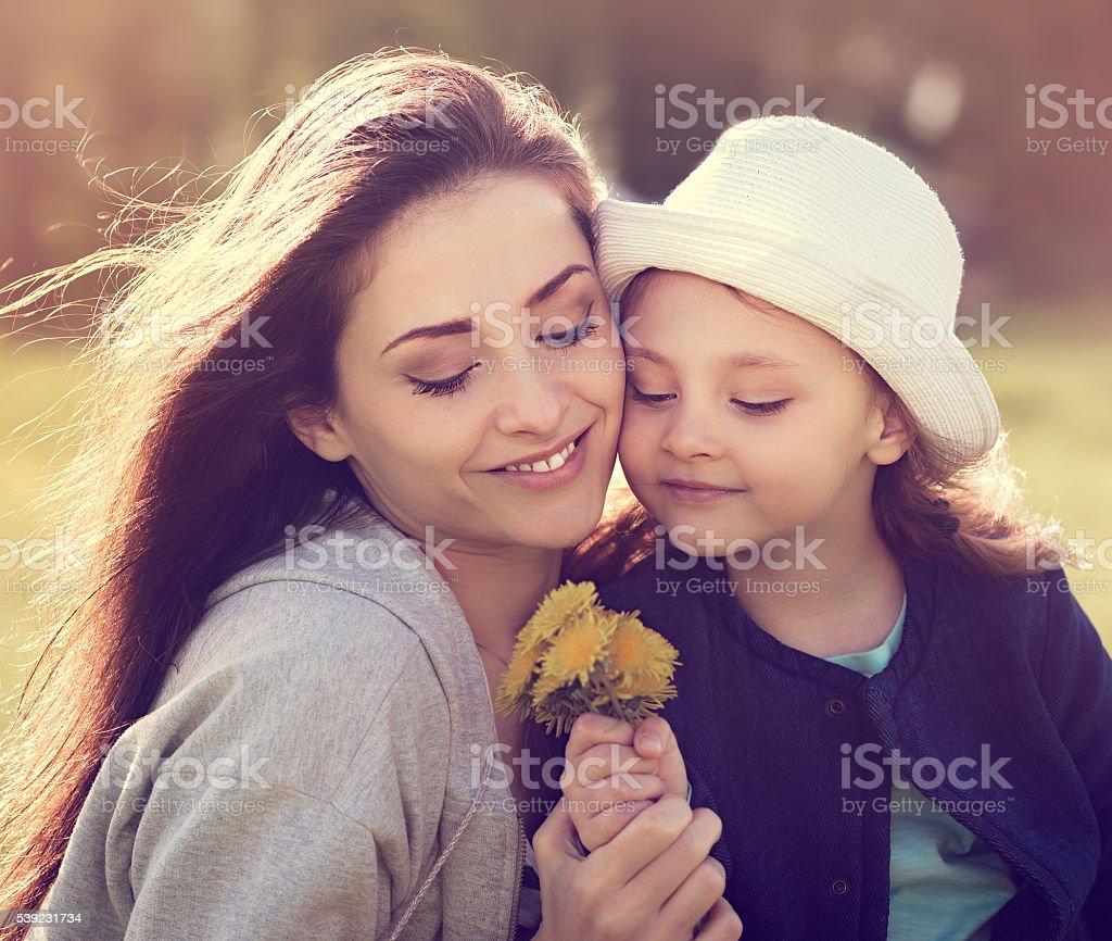 Feliz sorrindo a Mãe abraça a filha no chapéu, olhando foto royalty-free