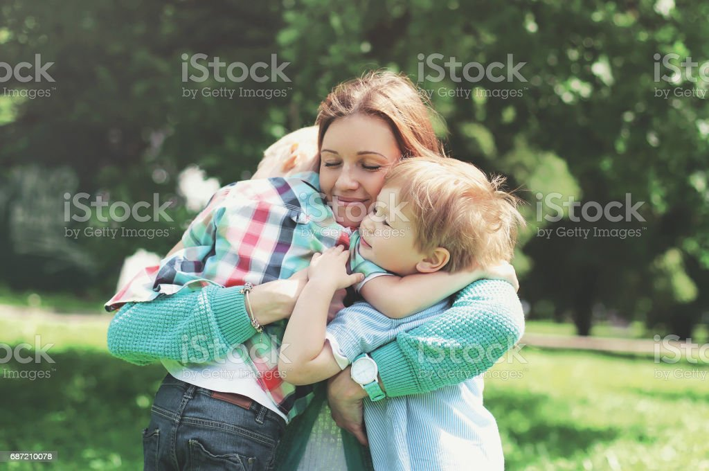 Happy smiling mother is embracing children at summer day stock photo
