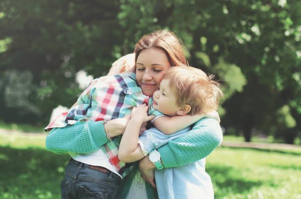 glücklich lächelnde mutter umarmt kinder am sommertag - russisch hallo stock-fotos und bilder