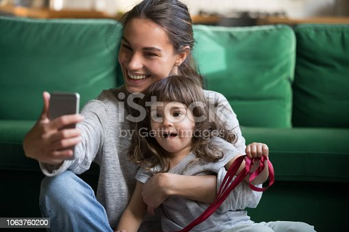 1063760138 istock photo Happy smiling mother taking selfie with daughter 1063760200