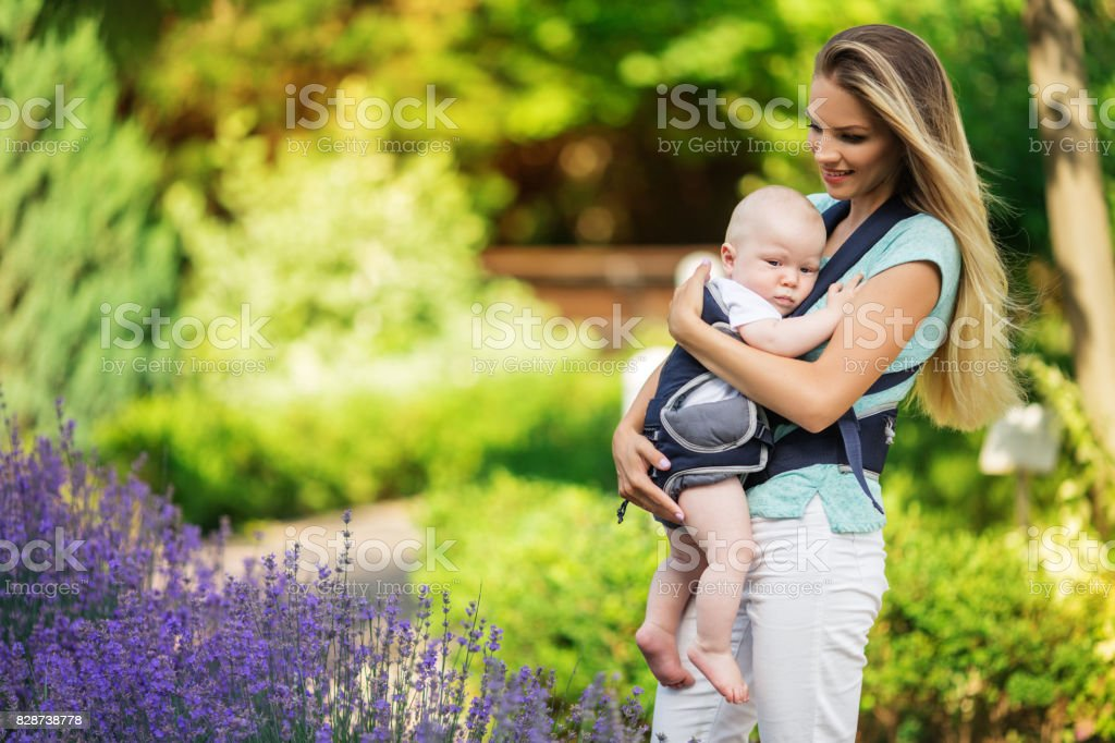 400974c4c1b Happy smiling mother with baby boy in sling walking in park royalty-free  stock photo