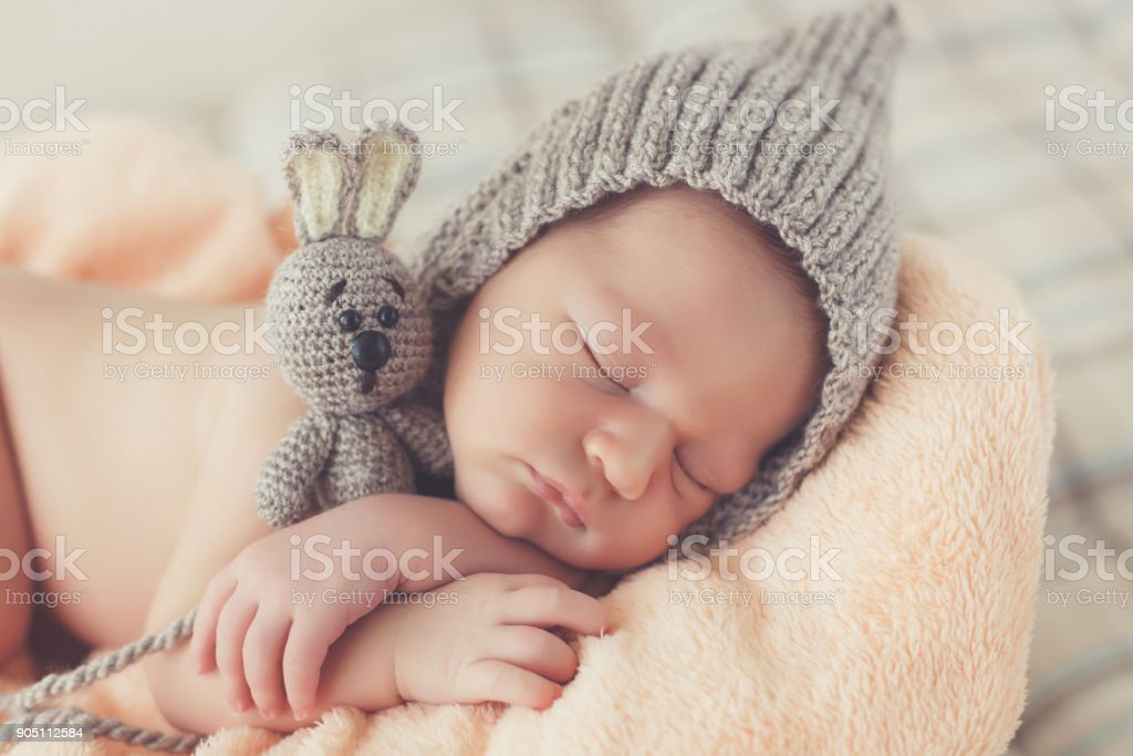2bbb20b3d98 Happy smiling newborn baby boy in knitted hat soundly sleeping in basket  royalty-free stock