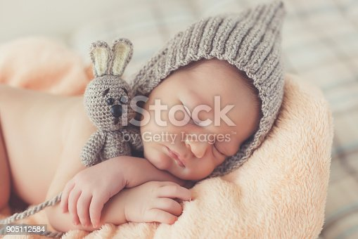 istock Happy smiling newborn baby boy in knitted hat soundly sleeping in basket 905112584