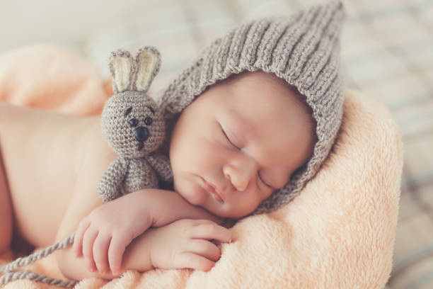 Happy smiling newborn baby boy in knitted hat soundly sleeping in basket stock photo