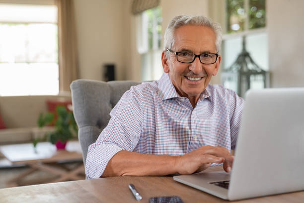 Happy smiling old man with laptop Smiling senior man looking at camera while using laptop at home. Handsome old man wearing eyeglasses working on laptop in living room. Portrait of elderly grandfather using computer. one senior man only stock pictures, royalty-free photos & images