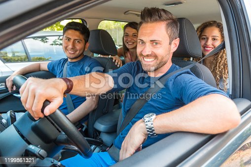 Happy smiling people sharing car ride - multicultural group of friends leaving for a trip together or sharing the ride to reduce emissions - sharing economy as well as friendship concepts