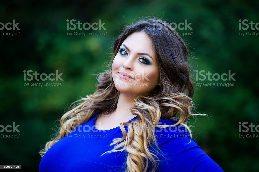 Happy smiling plus size model outdoors, xxl woman on nature stock photo