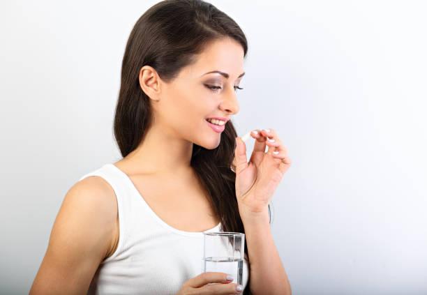 행복 하 게 웃는 긍정적인 여자 피임약 먹고 흰색 바탕에 손에 물 잔을 들고. 근접 촬영 프로필 보기 초상화입니다. - 마그네슘 뉴스 사진 이미지