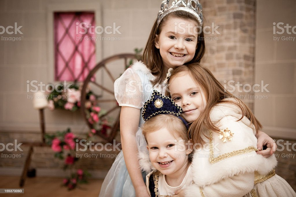 Happy, Smiling Princesses Hugging Each Other,With Castle Background stock photo