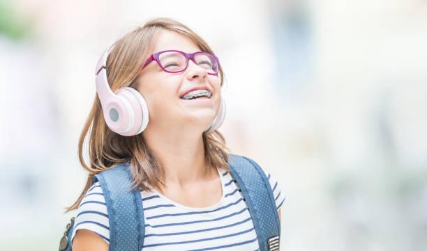Fröhlich lächelnde Schülerin mit Zahnspangen und Gläsern hören Musik von Kopfhörern ..  Kieferorthopäde und Zahnarzt Konzept. – Foto