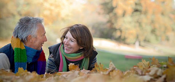 Happy smiling Senior couple lying on leaves in autumn stock photo