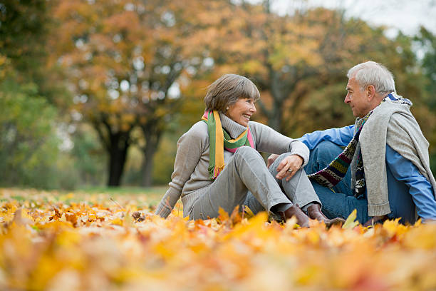 Happy smiling Senior couple sitting on leaves in autumn stock photo