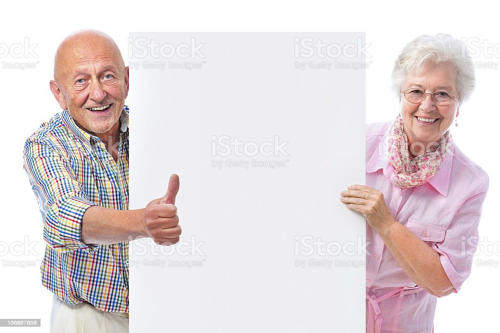 happy smiling senior couple with a blank board stock photo