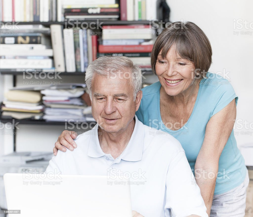 Happy smiling senior couple working at laptop royalty-free stock photo