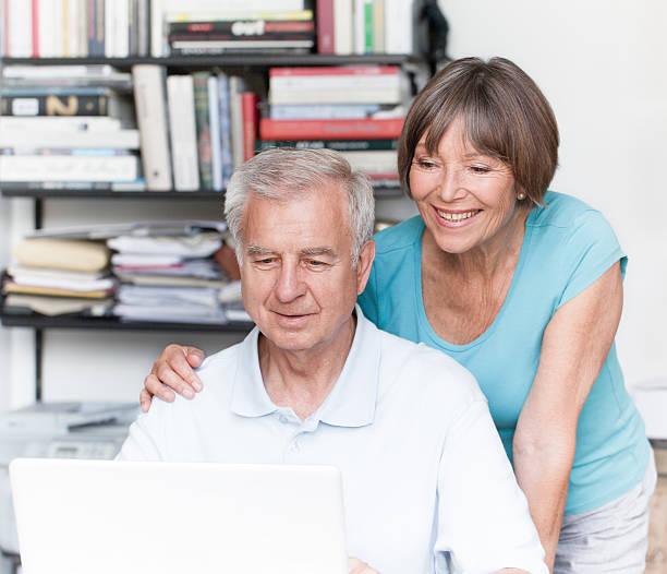 glückliches lächeln altes paar arbeiten am laptop - sanft und sorgfältig stock-fotos und bilder