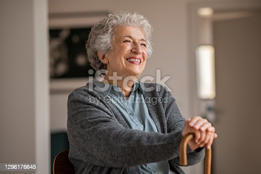 Retired senior woman laughing with her wooden walking stick while relaxing at home. Happy smiling old woman holding walking cane and looking through the window with positivity. Carefree smiling grandmother sitting on chair and looking away in nursing home.