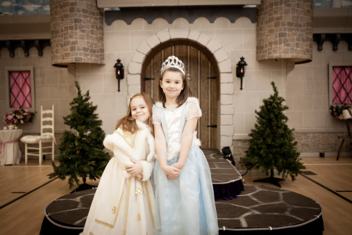 Happy, Smiling Sisters Dressed as Princesses, With Castle Background