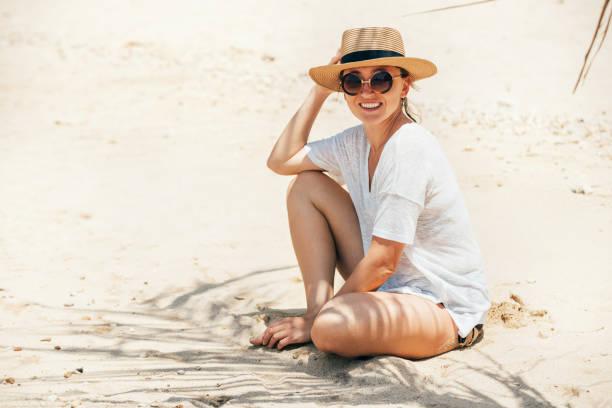 Mujer feliz sonriente tomando el sol en retrato de sombrero de paja. Sombras de palmeras en la arena. Imagen de concepto de bronceado saludable y vacaciones. - foto de stock