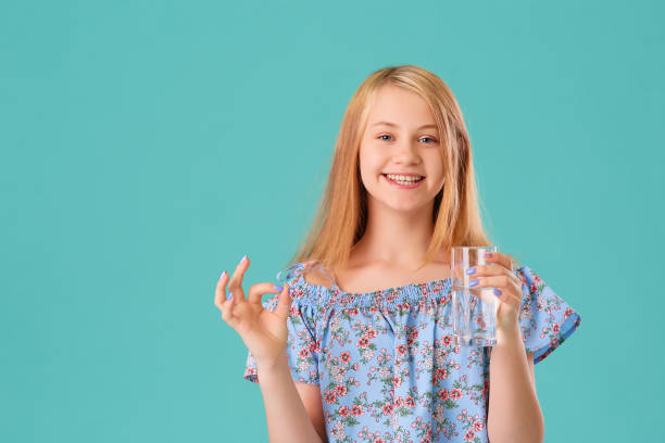 Happy smiling teen girl with a glass of water, she adheres to a drinking regime. Studio portrait on a turquoise background. Concept of health care and replenishment of the water-salt balance. stock photo