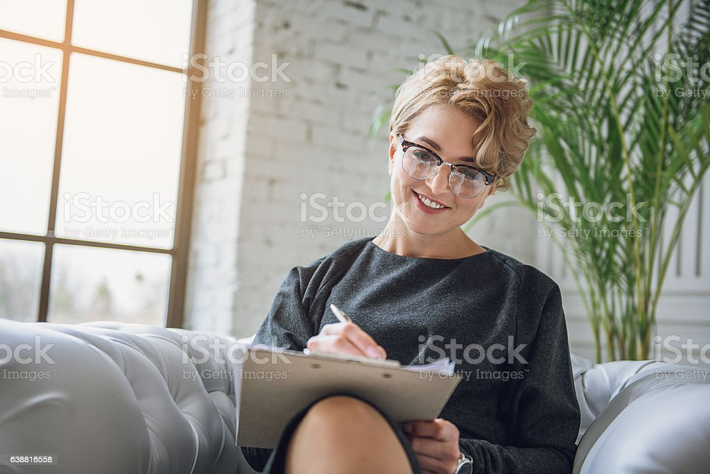 Happy smiling woman absorbedly writing stock photo