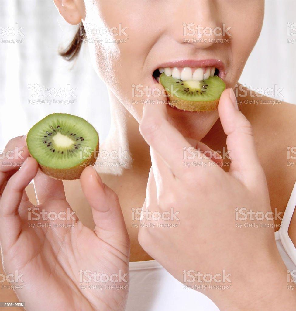 happy smiling woman bite a kiwi royalty-free stock photo