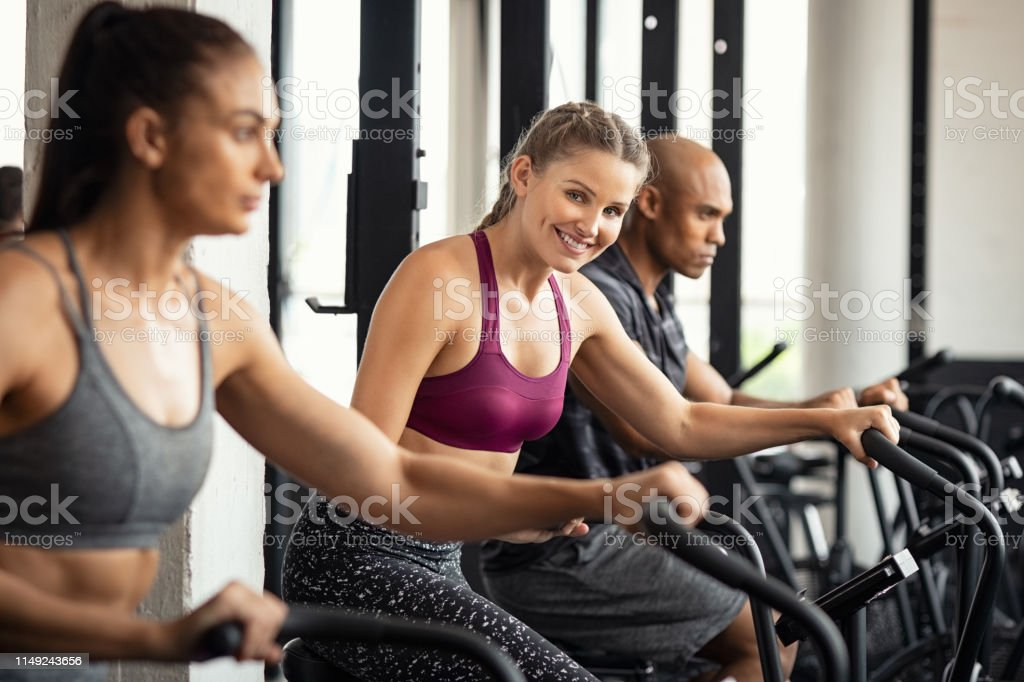 Fit woman working out with class on stationary bike at gym. Portrait...