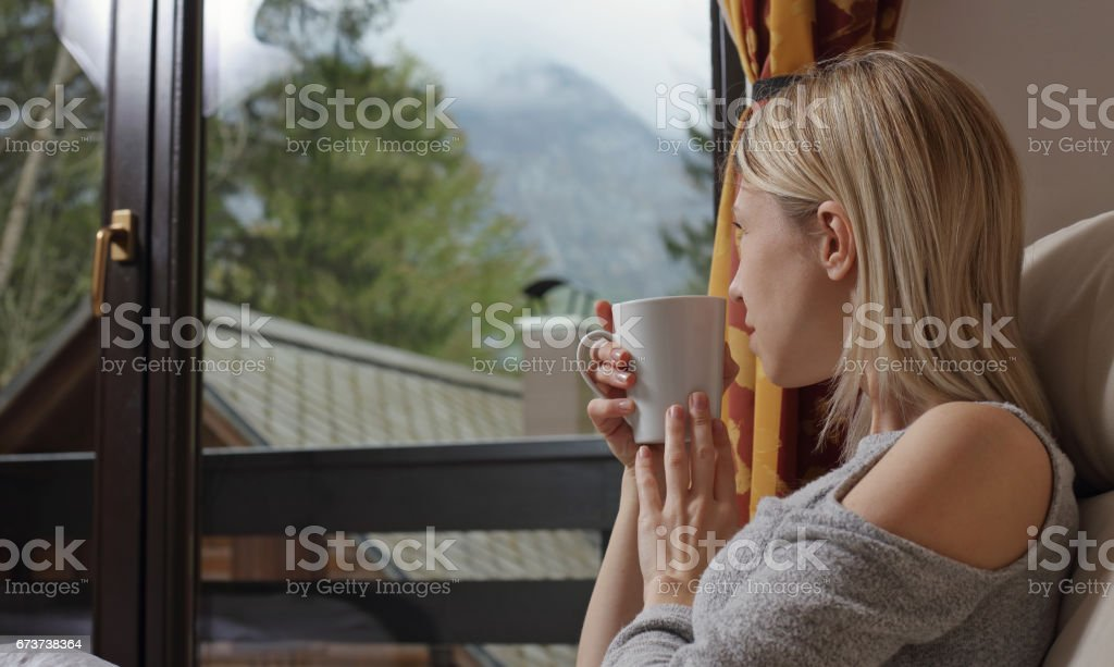 Happy smiling woman drinking hot tea by the window of country house with mountain view. Cozy lifestyle royalty-free stock photo