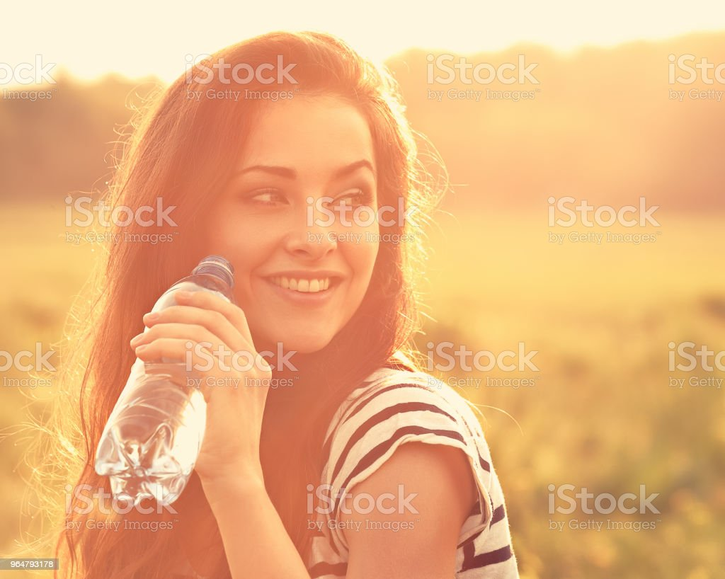 Happy smiling woman drinking water from the bottle on summer bright outdoor background. Closeup toned orange portrait royalty-free stock photo