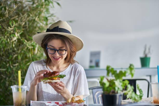 Glücklich lächelnde Frau, die einen gesunden veganen Burger im trendigen Restaurant isst – Foto