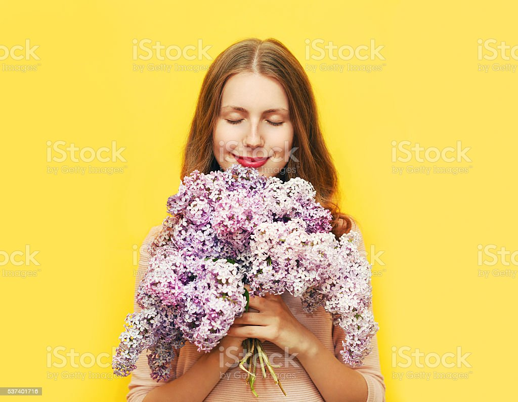 Happy smiling woman enjoying smell bouquet lilac flowers over yellow stock photo
