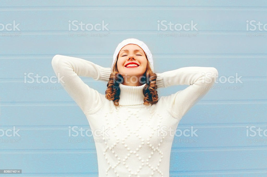Happy smiling woman enjoys good day wearing knitted hat, sweater stock photo