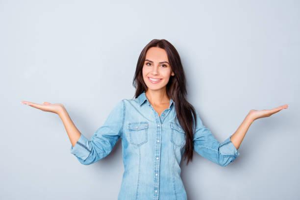 glücklich lächelnde frau mit händen gestikulieren und zeigen gleichgewicht - damen jeans sale stock-fotos und bilder