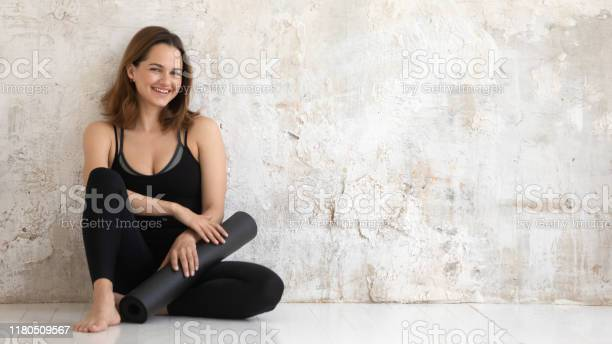 Happy smiling woman holding black yoga mat sitting on floor picture id1180509567?b=1&k=6&m=1180509567&s=612x612&h=bz0kmunlcuoaci9ewvyn1fchblv6le1gb0agz7eag3q=
